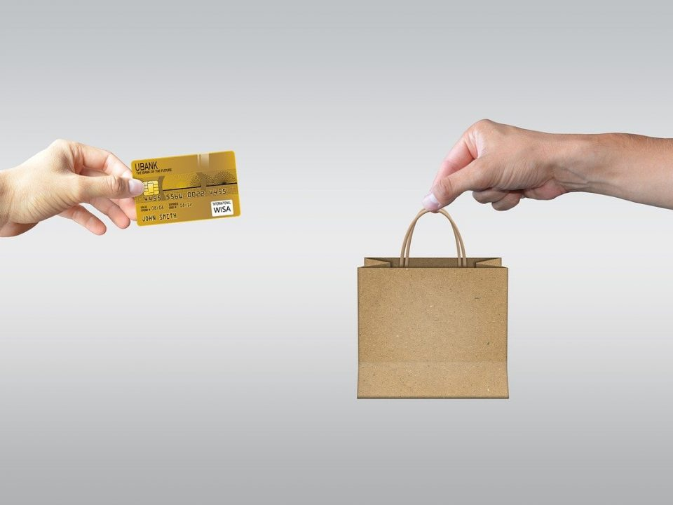 On the left hand holding a credit card reaching out of a computer, on the right hand holding a shopping bag reaching out of another computer. Symbolizing e-commerce.